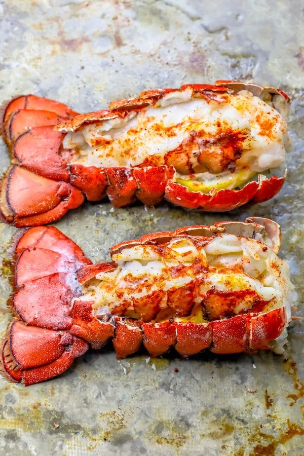 Picture of two broiled lobster tails on a baking sheet.