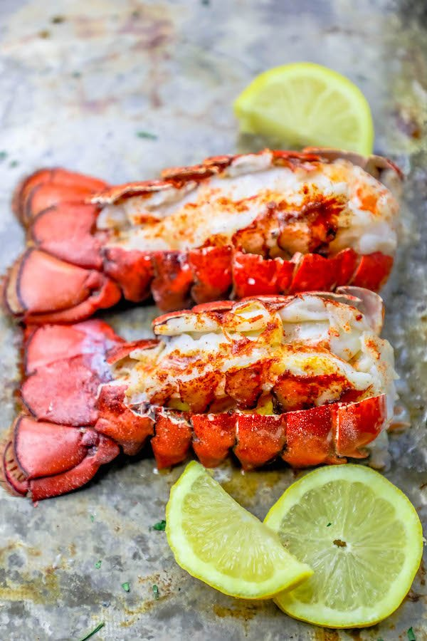 Picture of two broiled lobster tails on a baking sheet with lemon wedges.