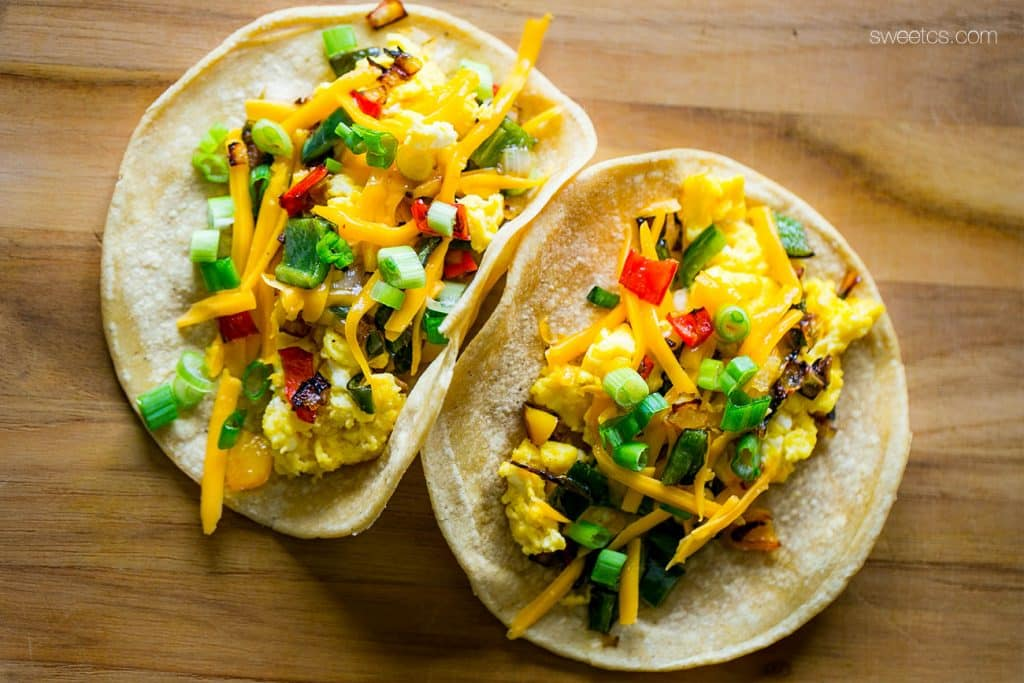 These spicy breakfast tacos are fileld with roasted poblano and bell peppers, caramelized onions, and cheesy scrambled eggs - wake up to a fiesta!