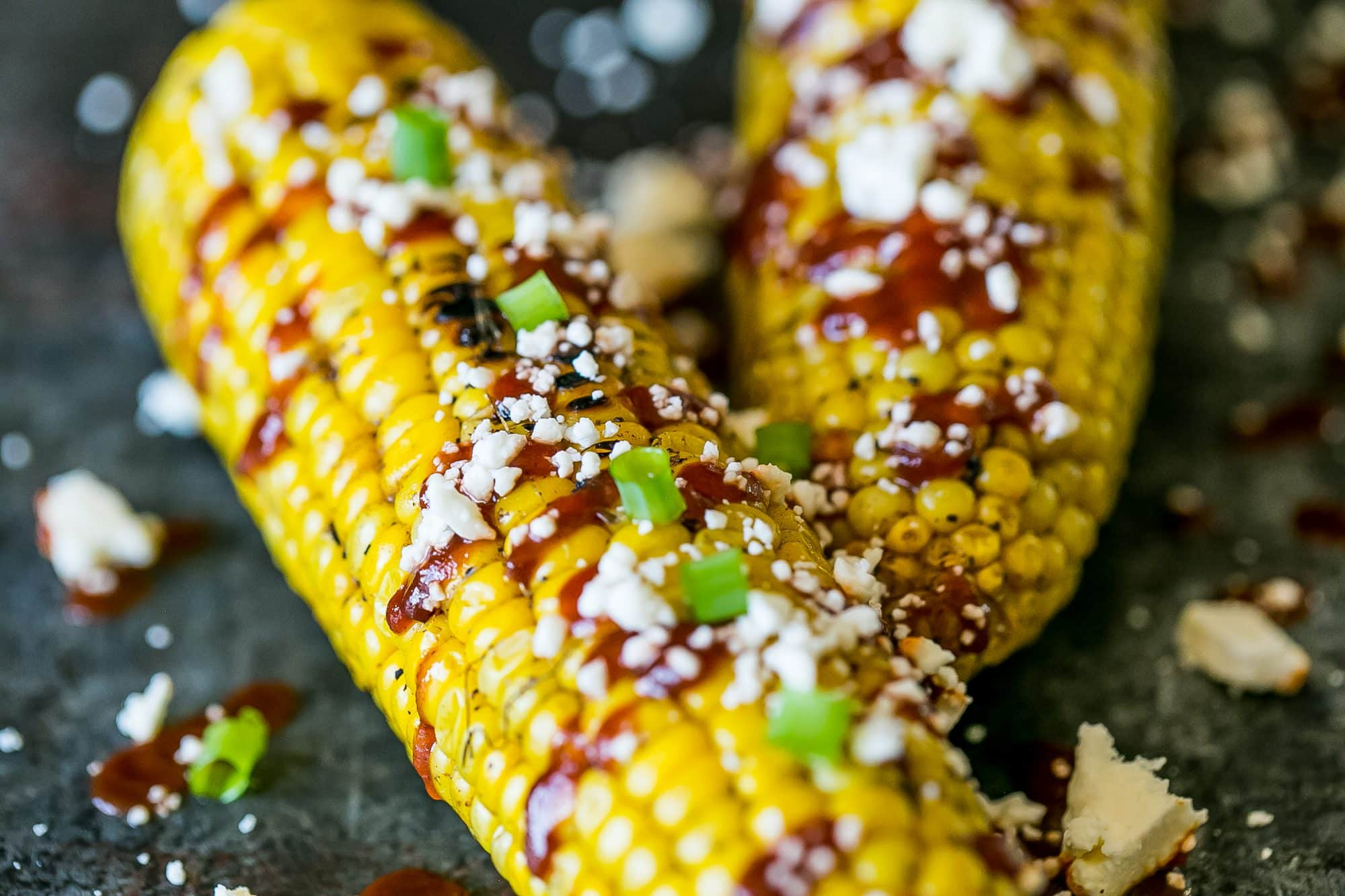 quick and easy mexican style street corn on the cob - with cotija cheese and sriracha!