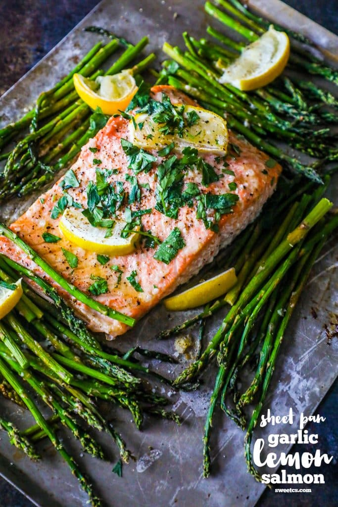 picture of salmon and asparagus on a baking sheet with lemons and parsley on top of it
