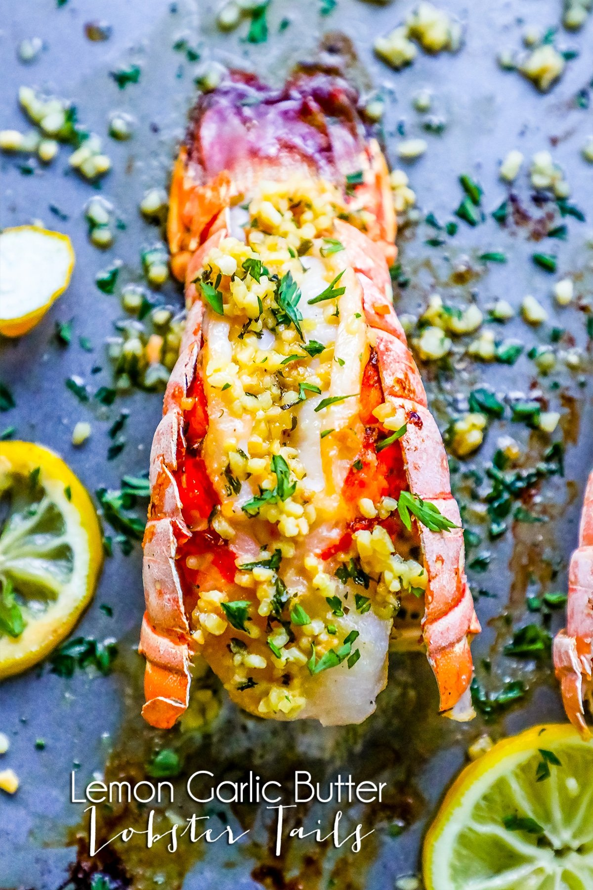 picture of lobster on baking sheet with lemon and parsley on top