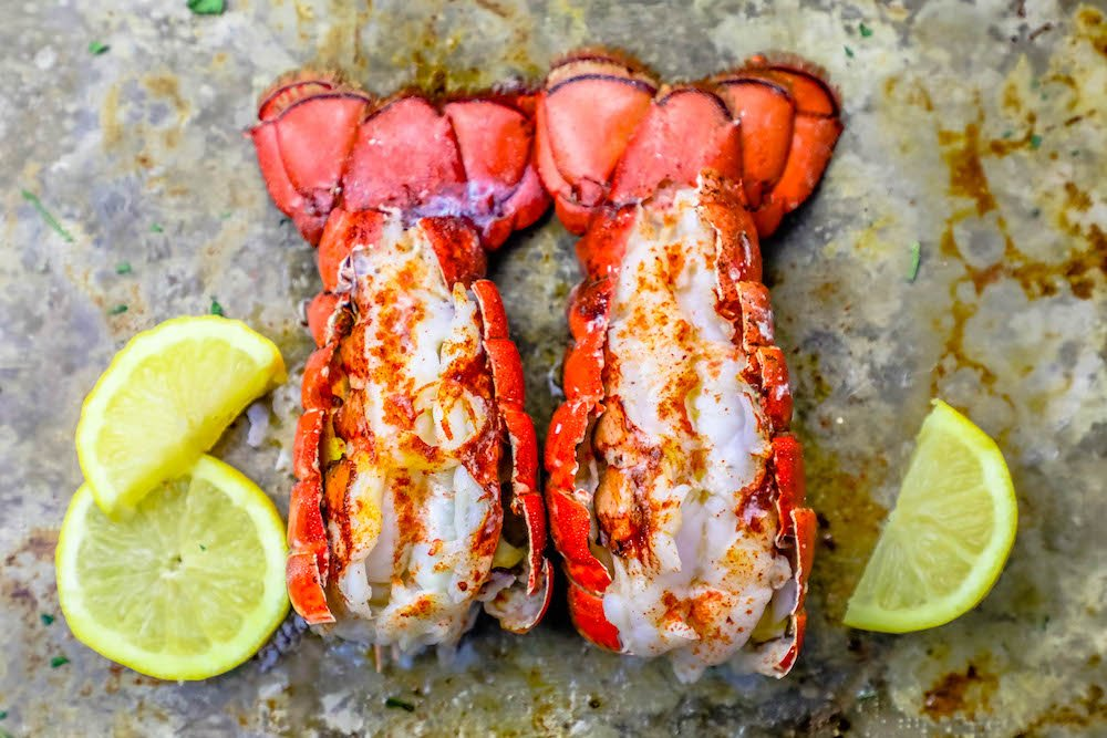 Picture of two broiled lobster tails on a baking sheet with lemon slices.