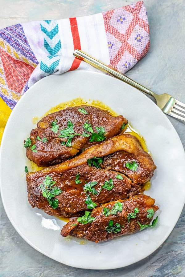 picture of pork steaks on a white plate with a bright colored napkin and fork