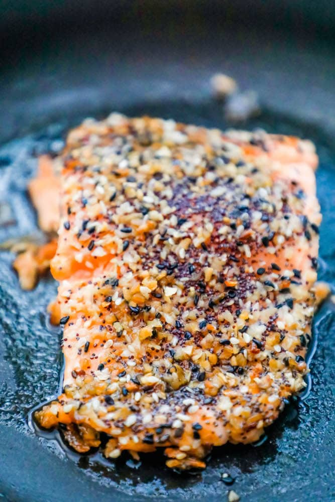 salmon filet in a pan after baking with everything bagel seasoning