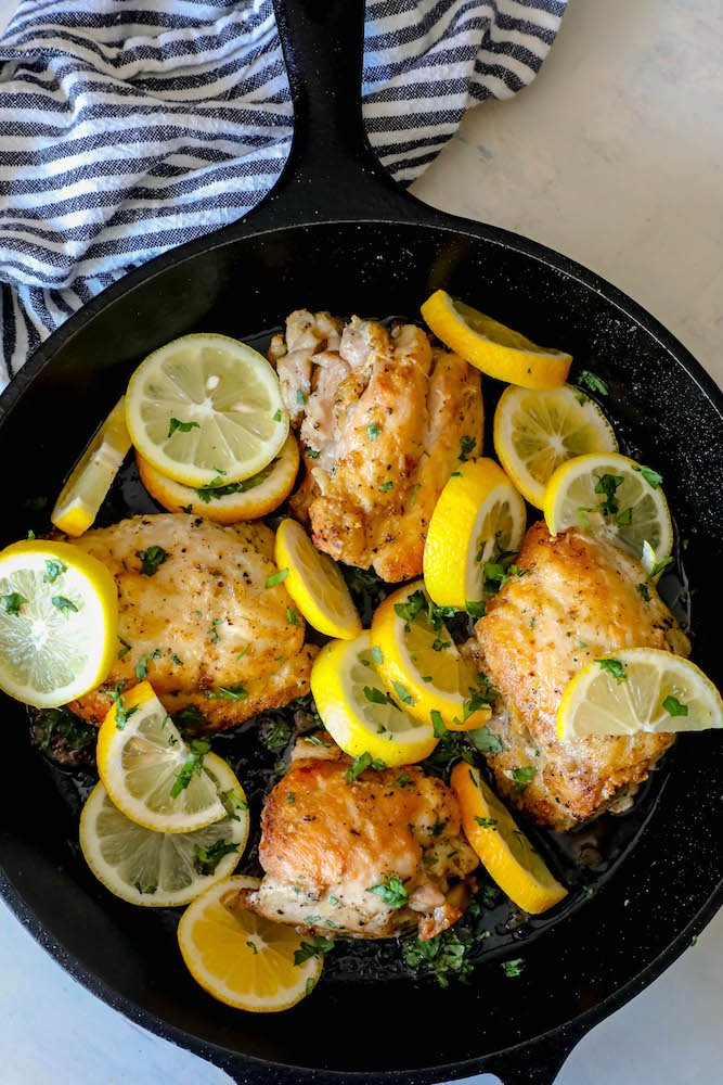 cast iron skillet with chicken thighs and sliced lemons in it
