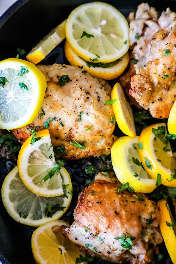 Chicken thighs in a pan with lemons