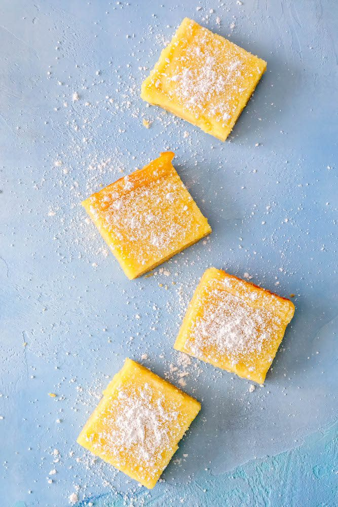 picture of 4 lemon bars on a table with powdered sugar