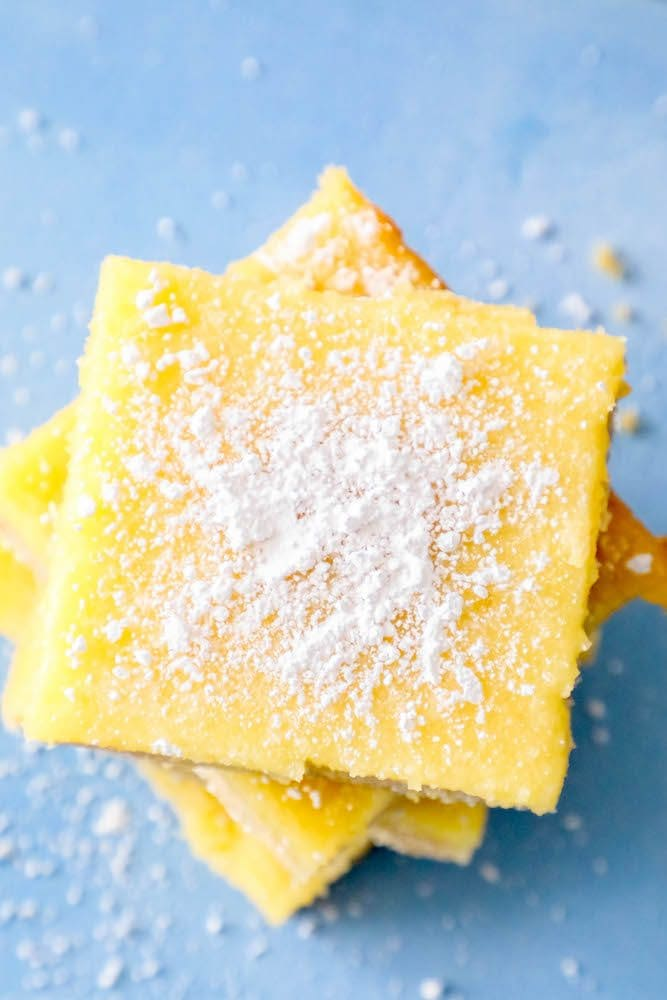 picture of lemon bars stacked on top of each other with powdered sugar sprinkled on top