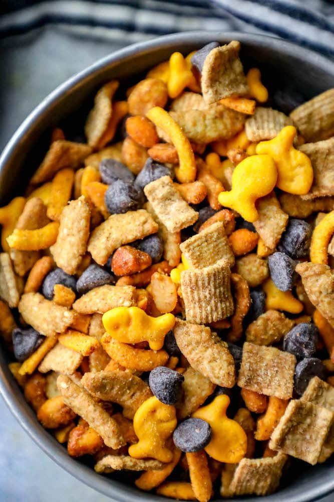 picture of guinness snack mix with goldfish crackers, graham crackers, chocolate chips, sesame sticks, and spicy trail mix in a metal bowl