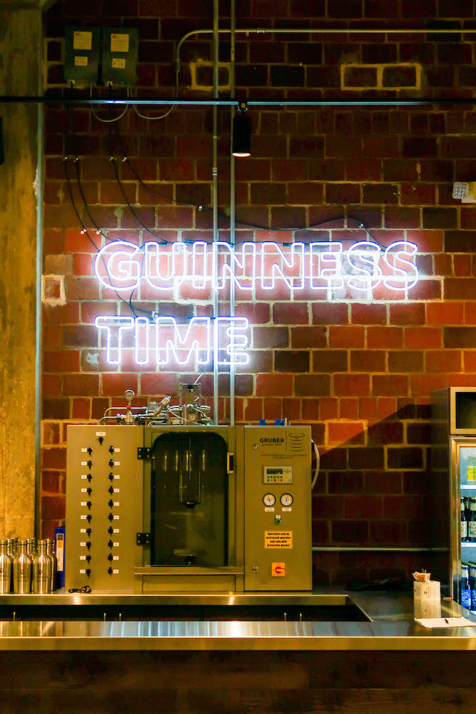 picture of neon light that says guinness time in a brewery