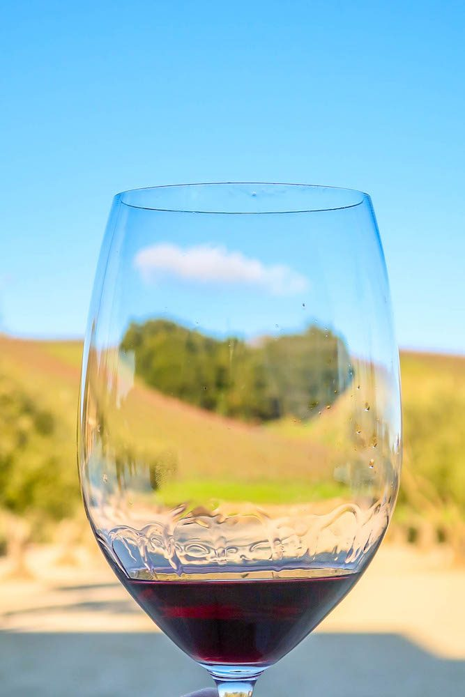 Picture of wine glass with hill shaped like heart in background