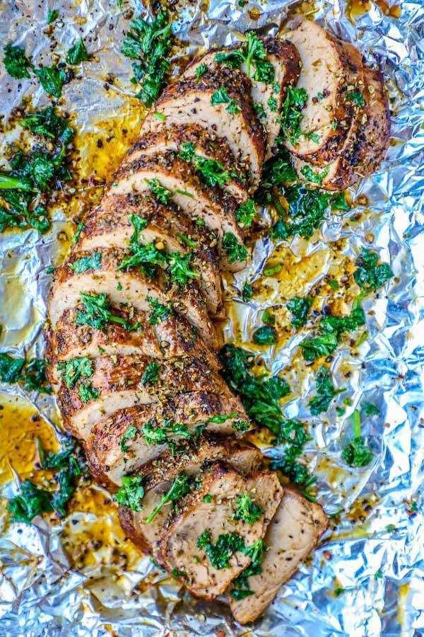 sliced garlic butter pork tenderloin on tinfoil lined baking sheet