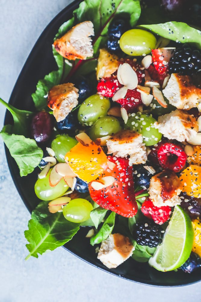 Picture of spinach salad with grapes, strawberries, blackberries, blueberries, raspberries, chicken, poppy seeds, hemp hearts, and a citrus poppyseed dressing on a black plate.