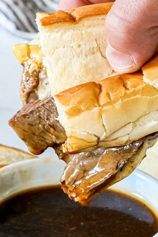 picture of french dip sandwich being dipped into au jus