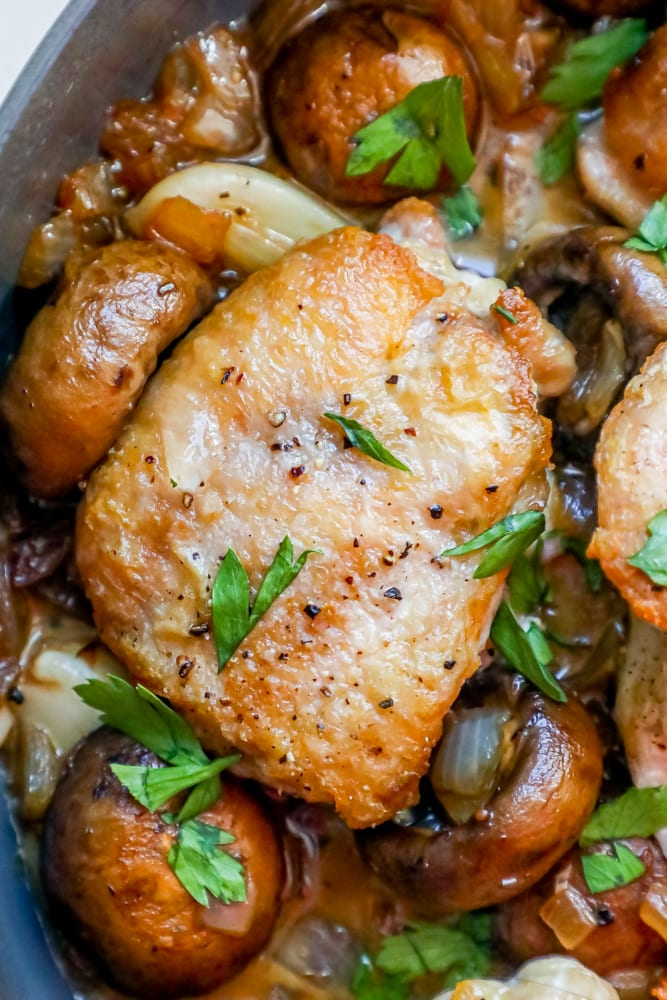 Picture of chicken thighs and mushrooms in a pan.