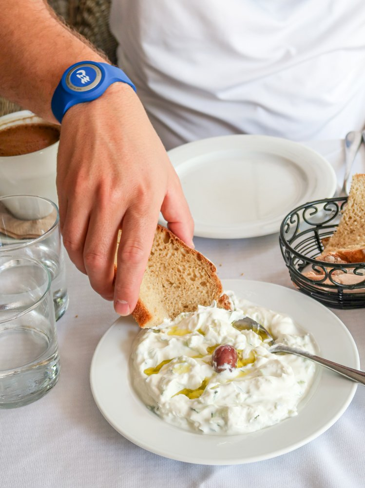 Picture of a hand dipping pita into tzatziki
