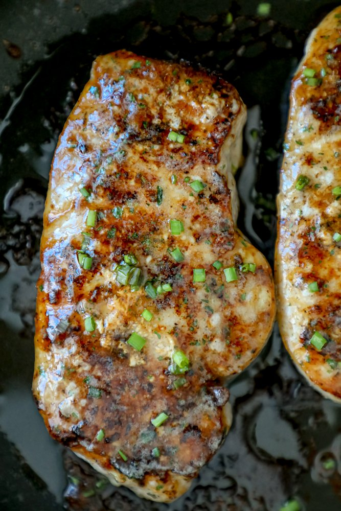 browned pork chops topped with ranch seasoning and chives in a black pan