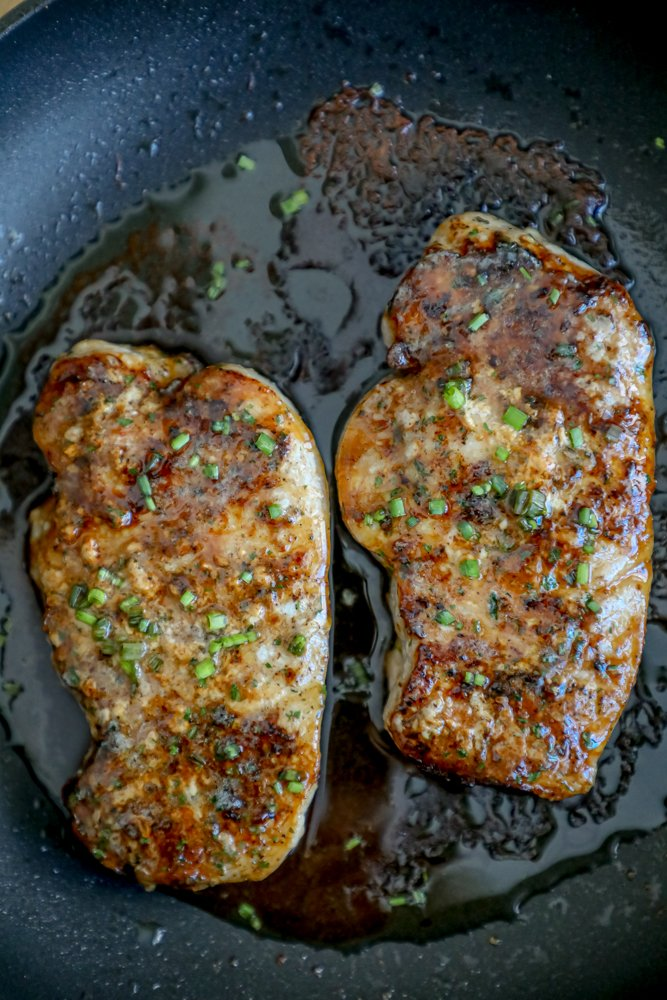 2 baked pork chops in a black pan with chives and ranch dressing seasoning on top