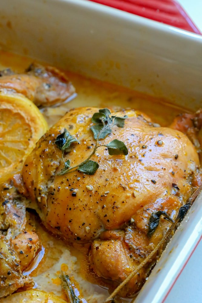 chicken in a baking dish with lemon and oregano