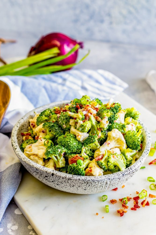 broccoli salad in a bowl and a cutting board with bacon and chives