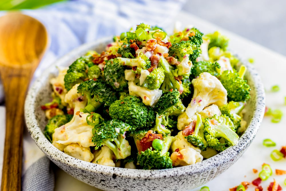 creamy broccoli keto salad in a bowl with a spoon on the side