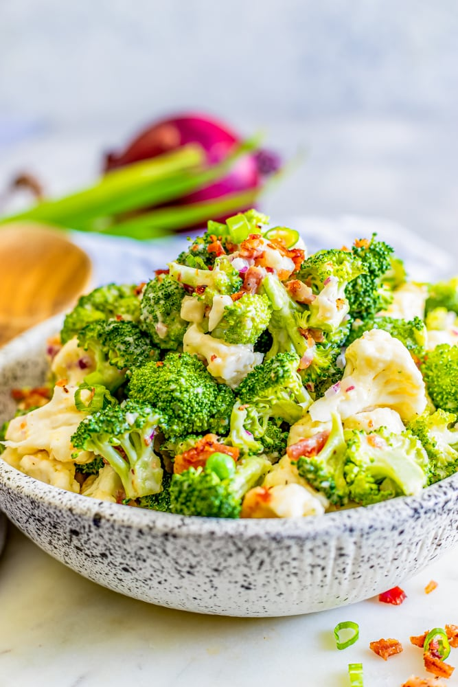broccoli and cauliflower salad in a bowl with creamy dressing