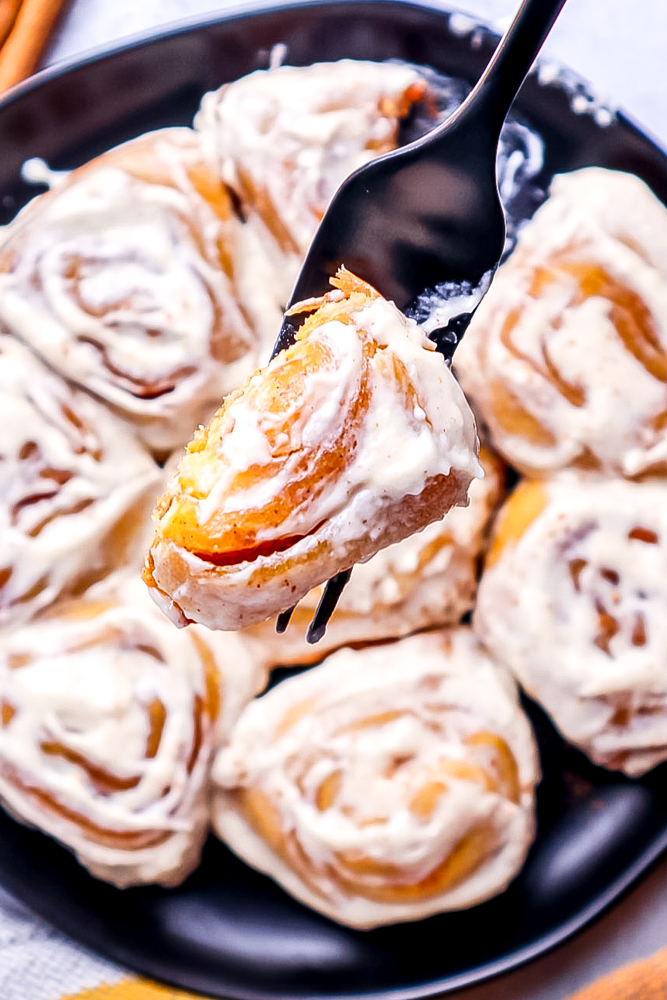 picture of a fork with cinnamon roll bite on it