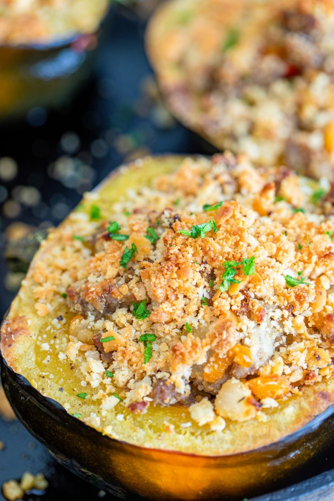 baked acorn squash stuffed with sausage and breadcrumbs on a baking sheet