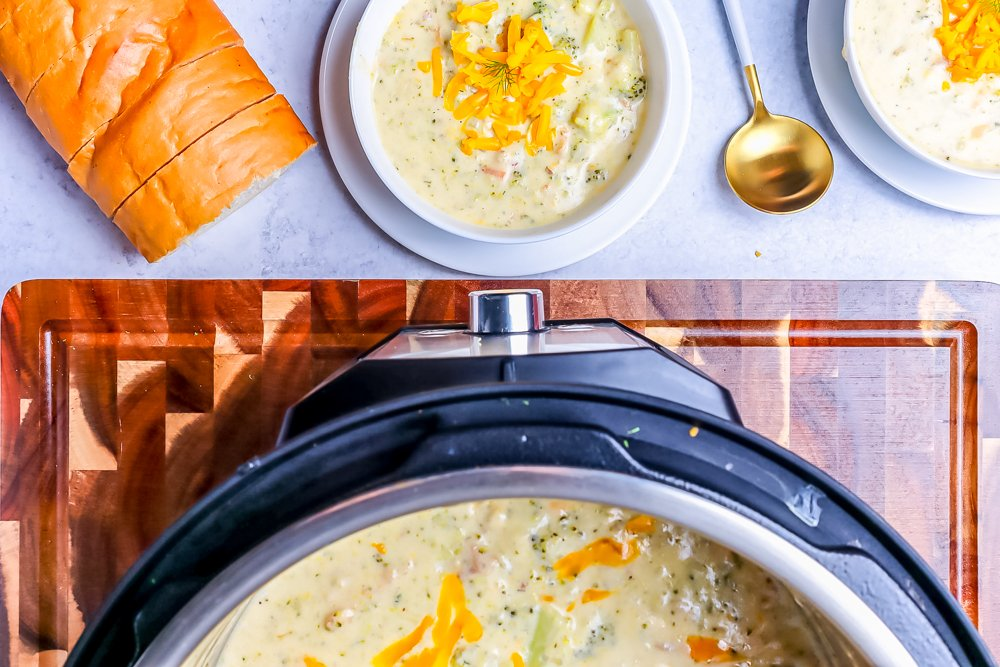 picture of instant pot and bowl with broccoli cheddar soup and bread