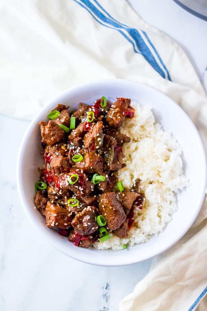 picture of korean beef in a bowl with scallions and rice