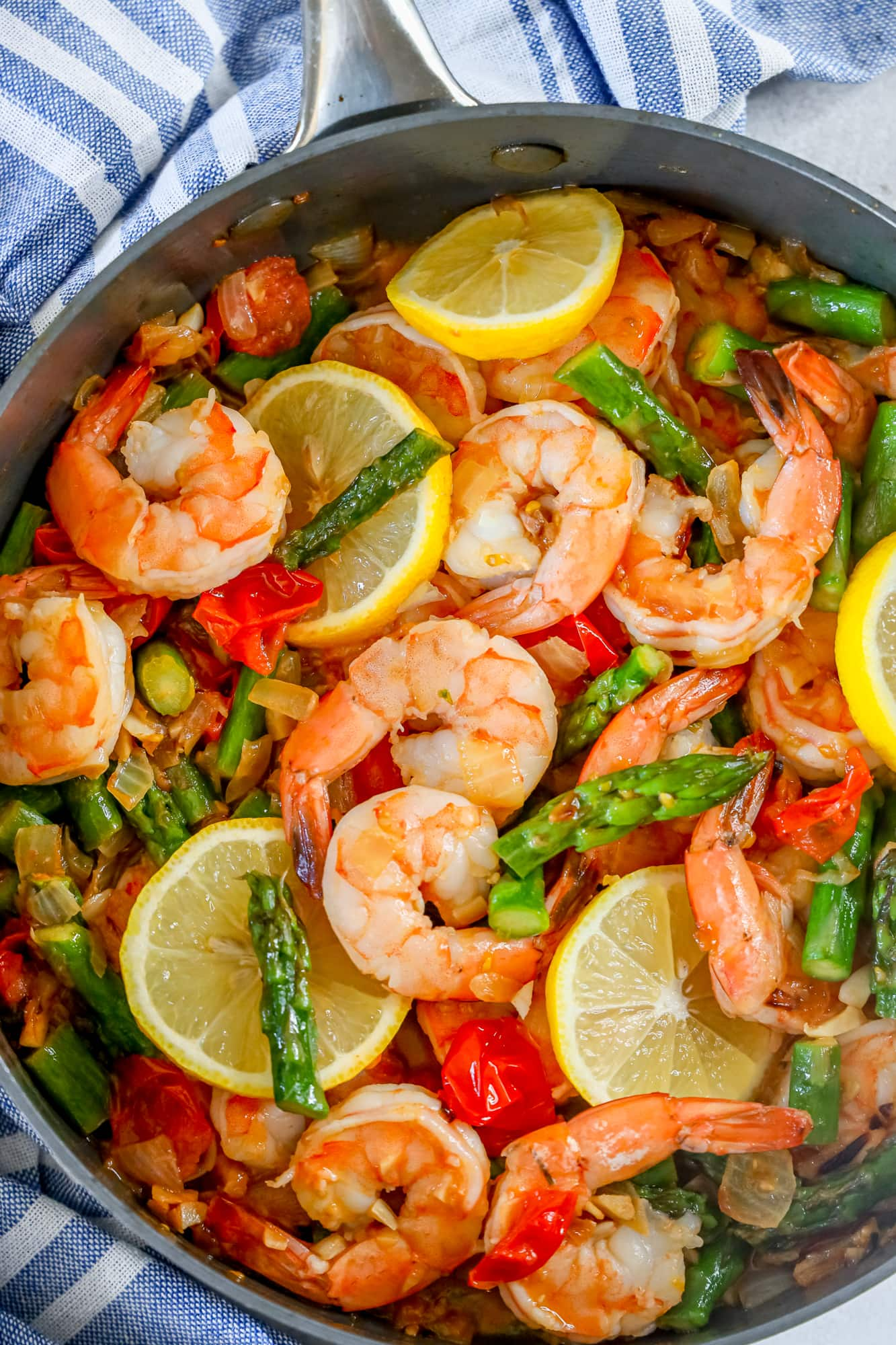 picture of shrimp, asparagus, cherry tomatoes, and lemons in a grey skillet