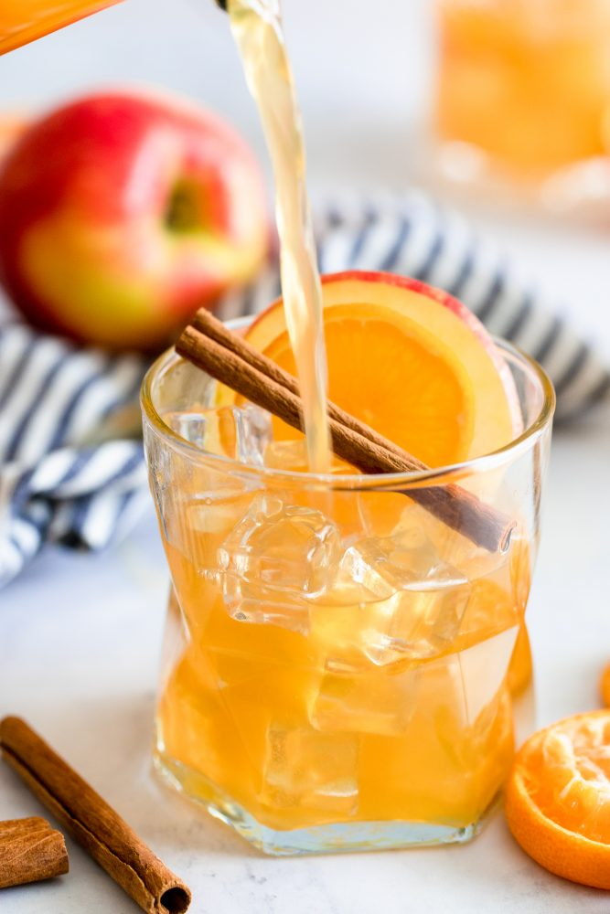 rum punch in a glass with an apple cinnamon stick and slice of orange