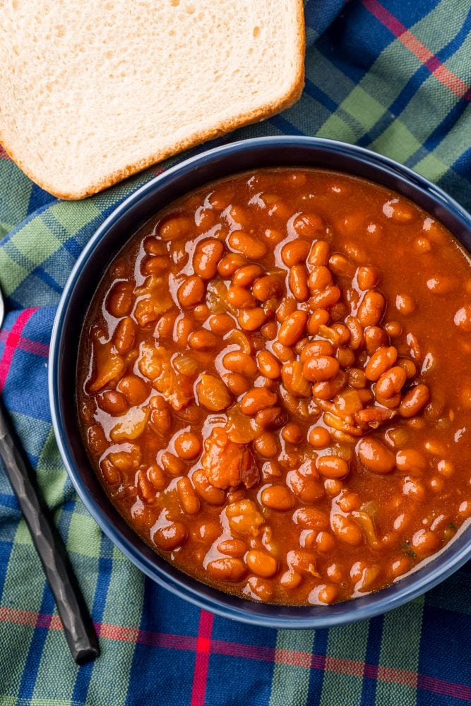 picture of baked beans in a blue bowl with a spoon on the table next to it