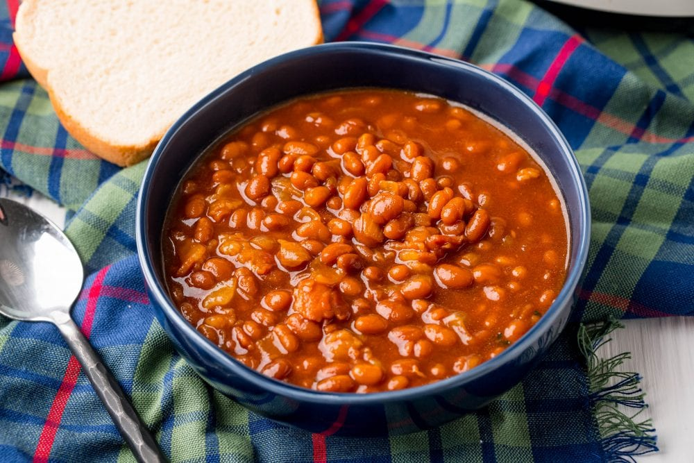 picture of baked beans in a bowl next to a slice of bread on a table