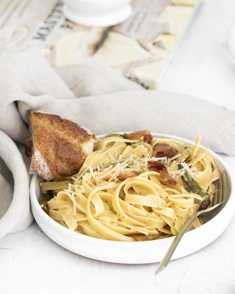 picture of a bowl with noodles, asparagus, parmesan cheese, bacon, and carbonara sauce