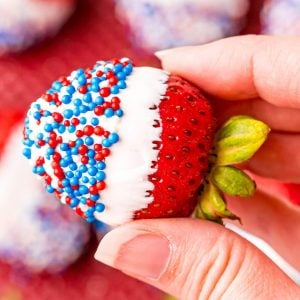 picture of a hand holding a strawberry dipped in white chocolate and sprinkles