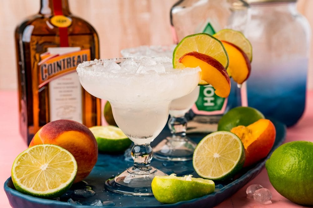 Picture of margarita glasses with peach slices in front of a bottle of tequila and a bottle of cointreau
