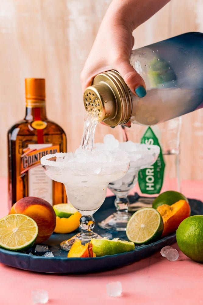 Picture of a hand pouring a margarita into a glass with peach slices in front of a bottle of tequila and a bottle of cointreau