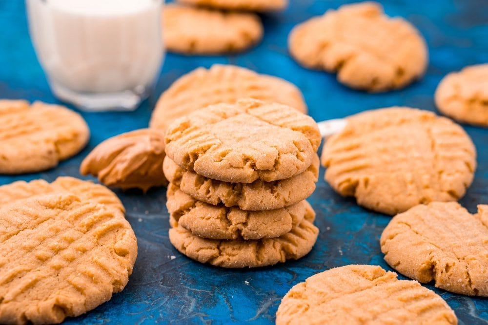 picture of peanut butter cookies stacked on a blue table