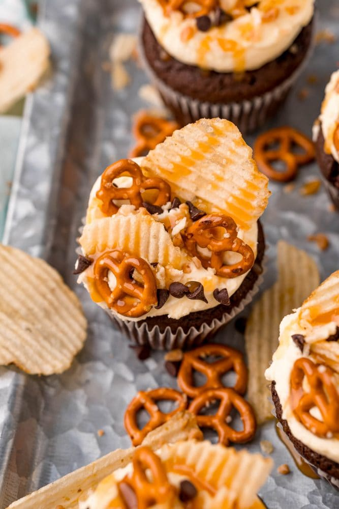 picture of cupcake topped with chips pretzels chocolate chips and caramel sauce