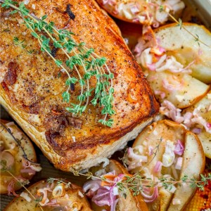 picture of pork loin in a roasting dish with roasted pears, shallots, and rosemary