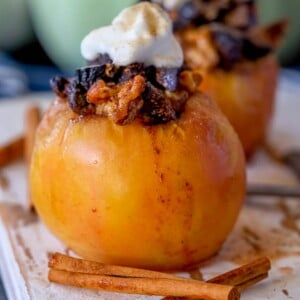 picture of baked apple on a plate topped with figs and whipped cream