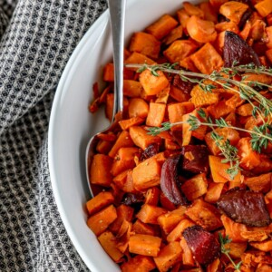 picture of roasted beets and sweet potatoes in a glass dish with thyme on top